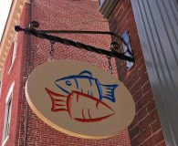 FARM & FISHERY – Paint Filled Carved Sign Mounted on a Scroll Bar in Philadelphia